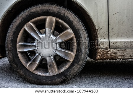 a weathered car wheel with mud and dirt - stock photo