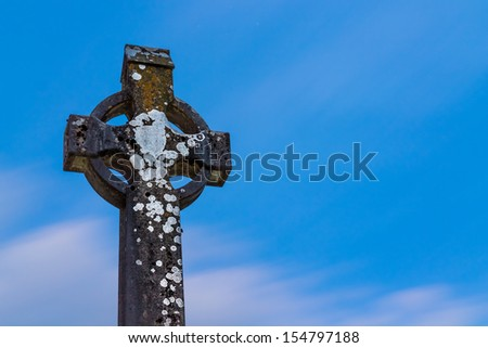 A weathered Celtic Cross against a deep blue sky