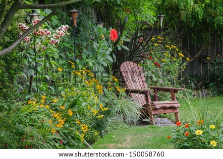 A weathered wood chair sits at the end of a stone walkway, hidden behind colorful zinnias. - stock photo