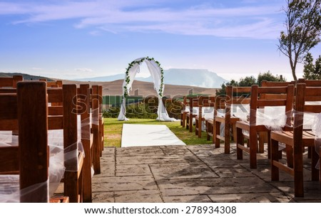A wedding arch of cloth and vines against a blue sky and landscape background showing chairs and lace - stock photo