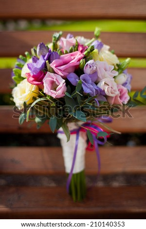 A wedding bouquet lies on the wooden bench in summer park  in evening.