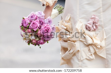 A wedding bouquet of pink and violet roses, creating a beautiful contrast with the big ribbons of the dress. - stock photo