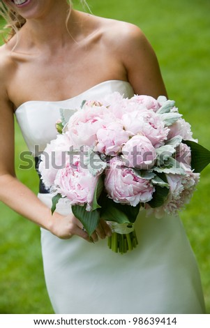 A wedding bouquet on pink flowers being held by a happy bride - stock photo