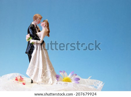 A wedding cake topper on top of the newlyweds dessert. - stock photo