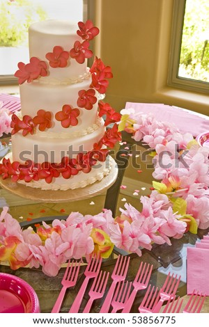 A wedding cake with red flowers surrounded  by pink flowers. - stock photo