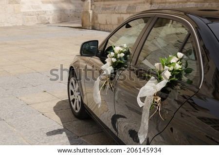 A wedding car decorated with bouquets of white roses - stock photo
