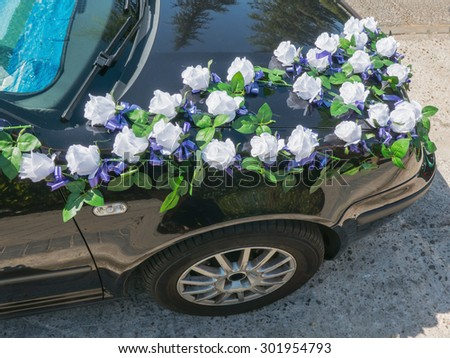 A wedding car decorated with bouquets of white roses