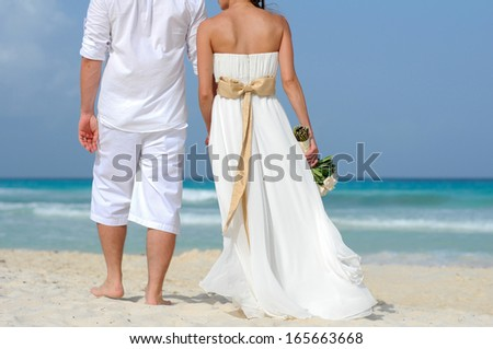 A wedding couple walking on the beach and holding hands - stock photo