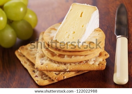 A wedge of brie cheese with crackers and grapes.