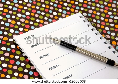 A weekly planner sits on a colorful tabletop - stock photo