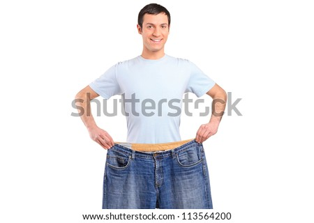 A weight loss male showing his old jeans isolated on white - stock photo