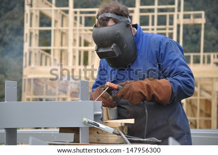 A welder prepares steel beams for a building at a construction site - stock photo