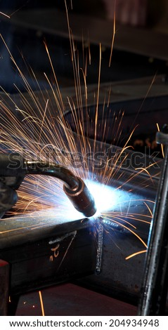 A welder welding the framework for industrial tanks - stock photo
