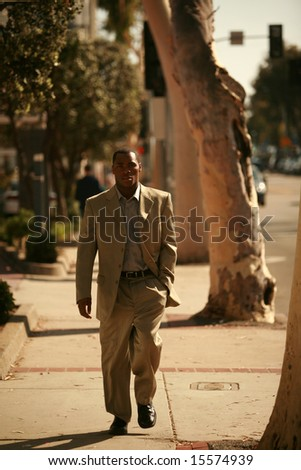 a well dressed american male model walks down a city sidewalk as if he is walking down a cat walk at a fashion show