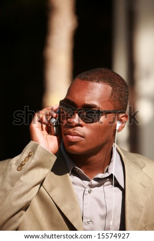 a well dressed business man recieves messages on his cell phone outside while listening on his personal digital music player