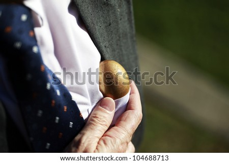 A well dressed businessman pulling a golden nest egg from his shirt pocket, indicating this nest egg comes from the heart.