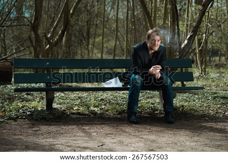 A well dressed depressed man sitting on a bench in a park smoking a cigarette with a suicide note next to him