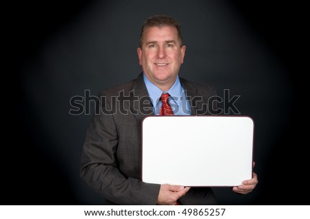 A well dressed professional businessman holds a blank whiteboard.  Board is left blank for designers to place copy.