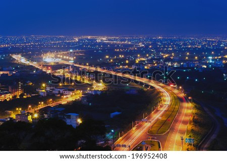 A well lit populated area at night with a brightly lit roadway winding through. - stock photo