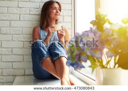 A well-pleased young girl enjoying an ideal day sitting in the window-sill. Wearing casual denim jeans and loose light-blue blouse, crossing legs and looking through the window