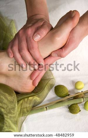 a wellness composition with a closeup of a foot of a mature natural woman having a foot massage - stock photo