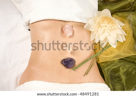 a wellness composition with a closeup of an abdomen of a natural mature woman with stones, flower and a silk scarf