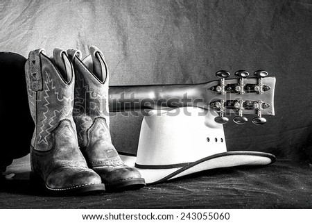 A western arrangement with cowboy boots, hat and an acoustic guitar.