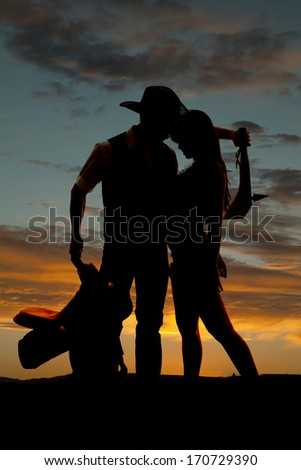 A western couple is standing in front of a sunset.  - stock photo