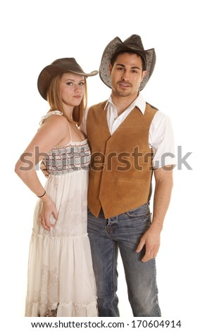 A western couple is wearing cowboy hats with serious expressions. - stock photo
