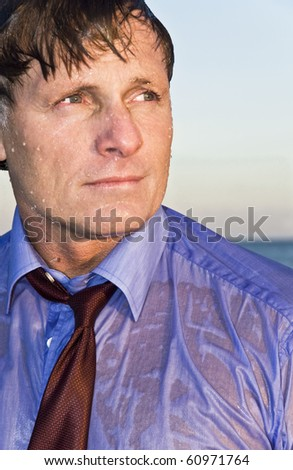 A wet businessman in his forties wearing a blue shirt and red tie.
