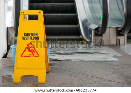 A wet floor sign and bucket at a spill in front of an escalator.