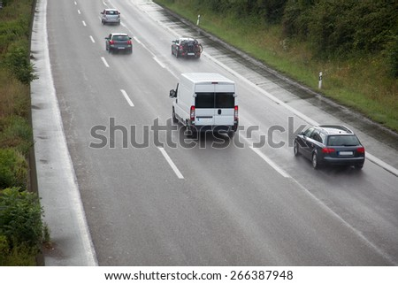 A wet highway with some dust and cars. - stock photo