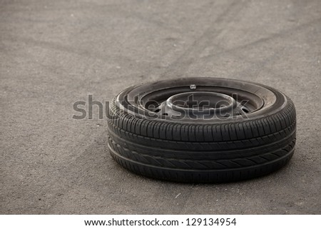 A wheel of a car left on the road - stock photo