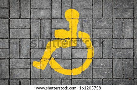 A wheelchair disabled man symbol imprint on a grungy brick pavement.  - stock photo