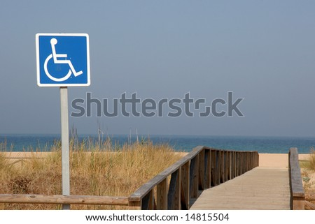 A wheelchair sign for easy access to the beach - stock photo