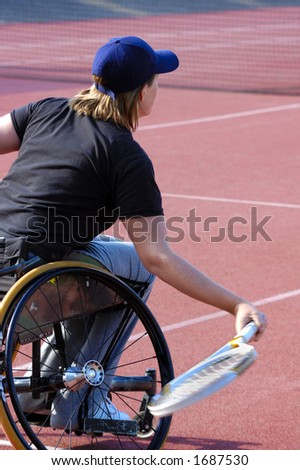 A wheelchair tennis player during a tennis championship match, returning a shot. Motion blur on her racket.