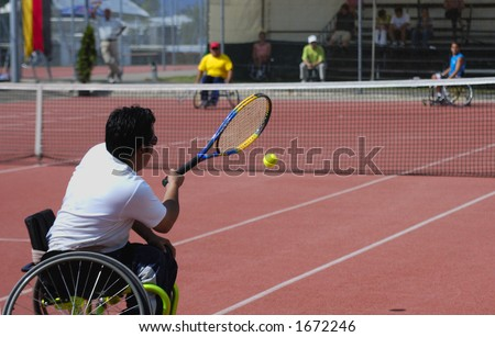 A wheelchair tennis player during a tennis championship match, taking a shot.