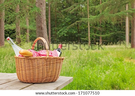 A whicker picnic basket full of food and drink on a table in a woodland setting on a bright summers day. - stock photo