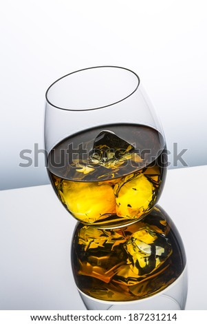 a whiskey glass with ice cubes Scottish and reflection drink and grey gradient background