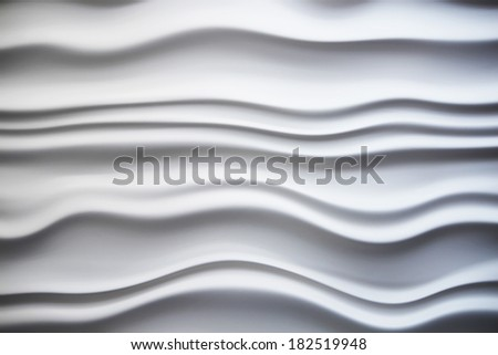 A white abstract wall with wavy lines throughout - stock photo