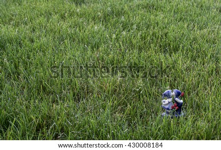 A white and blue figurine of a man and a woman in a field of grass - stock photo