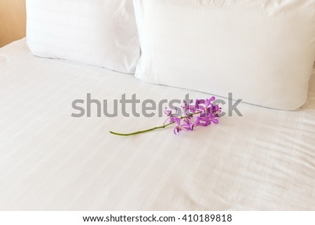 A white bed with 2 pillows and a flower