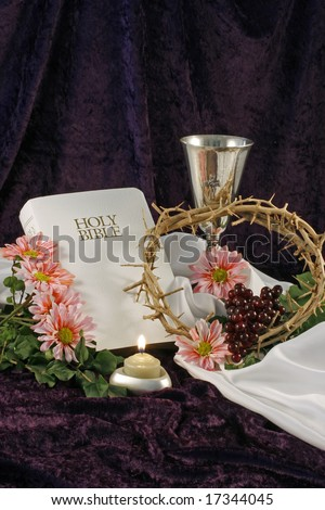 A white bible, chalice, flowers, crown of thorns, candle, pink daisies and grapes are displayed over a purple back drop with room for copy.