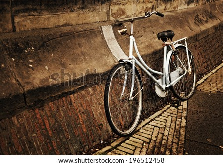 A white bike leaning against a cement wall. - stock photo