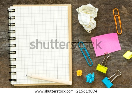 A white blank note book and pencil and office supplies for your message place on old color full table - stock photo