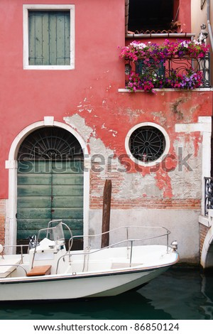 A white boat anchored by an old wall in Venice - stock photo