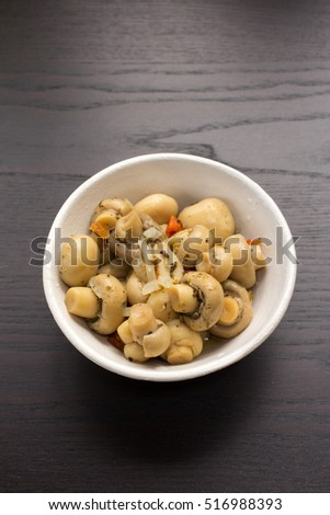 A white bowl full of marinated mushrooms.
