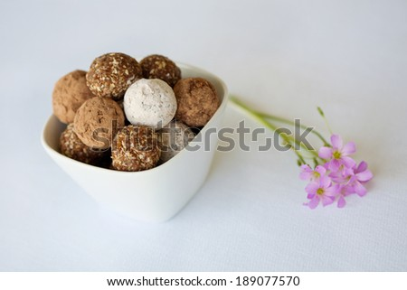 A white bowl of an assortment chocolate balls and rum balls presented with a purple flower on a white background.   - stock photo