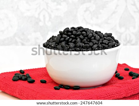 A white bowl of dried, healthy black turtle beans. - stock photo