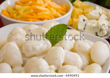 a white bowl of italian gnocchi with cheese sauce and herbs